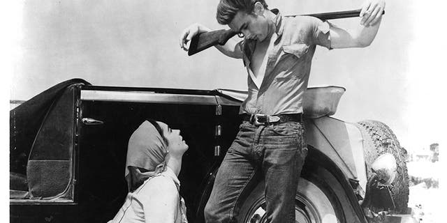 Elizabeth Taylor kneeling before James Dean in a scene from the film<br>