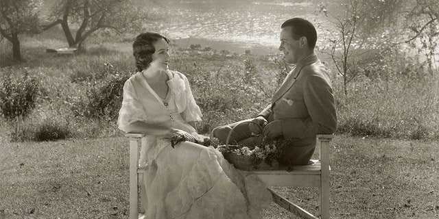 Actress Fay Wray sitting with her husband, the writer, John Monk Saunders, on a wooden bench in an outdoor setting near a lake.