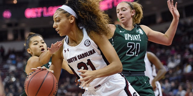 South Carolina's Harrigan Herbert (21) drives along the baseline while defended by South Carolina-Upstate's Riley Popplewell (21) and Maya Timberlake during the first half of an NCAA college basketball game Thursday, Nov. 21, 2019, in Columbia, S.C. (AP Photo/Richard Shiro)