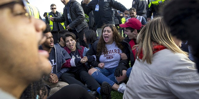 Harvard and Yale students protest during halftime of the NCAA college football game between Harvard and Yale at the Yale Bowl in New Haven, Conn., on Nov. 23, 2019. (Nic Antaya/The Boston Globe via AP)