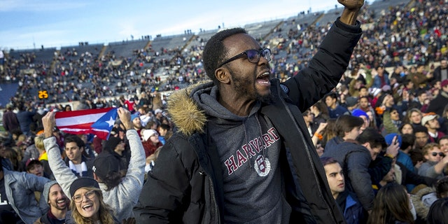 In this Saturday, Nov. 23, 2019, photo, Harvard and Yale students protest during halftime of the NCAA college football game between Harvard and Yale at the Yale Bowl in New Haven, Conn. Officials say 42 people were charged with disorderly conduct after the protest interrupted the game. (Nic Antaya/The Boston Globe via AP)