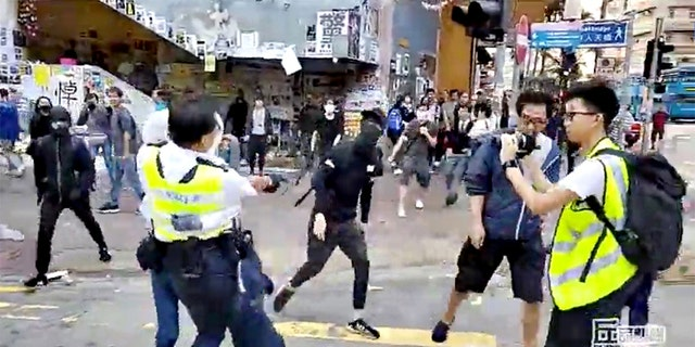 A still image from video showed a police officer aiming his gun as a protester in Hong Kong on Monday morning.