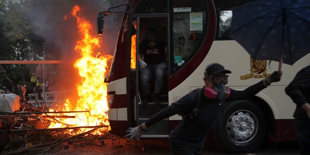 Students run past fire set near a bus during a face-off with riot police at the Chinese University in Hong Kong, Tuesday, Nov. 12, 2019.
