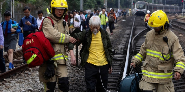 Firefighters help an elderly woman as commuters walk on the railway after their train service is disrupted by pro-democracy protesters in Hong Kong, Tuesday, Nov. 12, 2019.