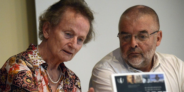"""German Inge Nedden (L), daughter of German WWII battleship Graf Spee's captain Hans Langsdorff, and Uruguayan writer Daniel Acosta y Lara (R) present his and Federico Leicht's book """"Graf Spee, from Wilhelmshaven to the River Plate"""", during the commemoration of the 75th anniversary of the Battle of the River Plate in Montevideo on December 13, 2014."""