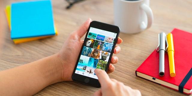 استانبول ، ترکیه - 2 فوریه 2019: زنی که از تلفن هوشمند روی میز چوبی استفاده می کند.  این تلفن هوشمند یک آیفون 8 است. آیفون یک گوشی هوشمند با صفحه لمسی است که توسط شرکت اپل تولید شده است.