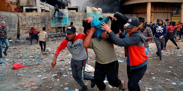 Political News: A wounded protester is carried to receive first aid during clashes in Baghdad Thursday. (AP Photo/Khalid Mohammed)