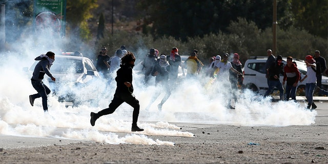 Palestinian demonstrators run from tear gas fired by Israeli troops during the protest against the U.S. announcement that it no longer believes Israeli settlements violate international law.