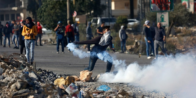 Palestinian demonstrator throws back tear gas fired by Israeli troops during the protest against the U.S. announcement that it no longer believes Israeli settlements violate international law., at checkpoint Beit El near the West Bank city of Ramallah, Tuesday, Nov. 26, 2019.