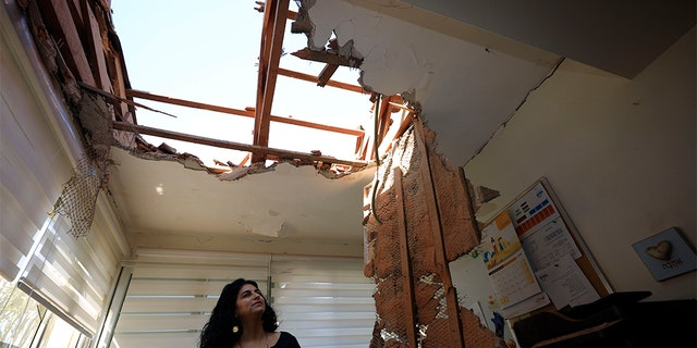 A woman surveys the damage to a house in Sderot, Israel, after it was hit by a rocket fired from Gaza Strip Tuesday.