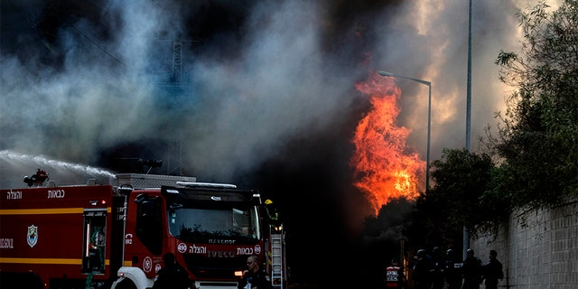 Firefighters deploy after a factory hit by a rocket caught fire in Sderot Tuesday.