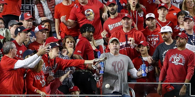 While holding two Bud Light beer cans, baseball fan, Jeff Adams, is hit in the chest with the home run ball hit by Yordan Alvarez #44 of the Houston Astros (not pictured) in the second inning during Game 5 of the 2019 World Series between the Houston Astros and the Washington Nationals at Nationals Park on October 27, 2019 in Washington, DC. (Photo by Patrick Smith/Getty Images)
