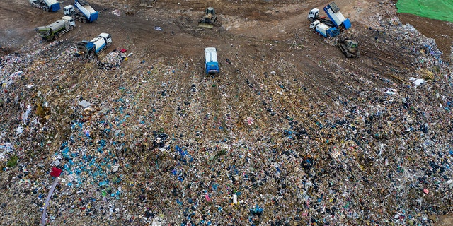Chinese workers sort out and bury kitchen waste at the Jiangcungou Landfill, which is the China's largest refuse landfill, in Xi'an city, northwest China's Shaanxi province, 21 August 2019. China's largest refuse landfill was set to close in October 2019 as it was almost saturated in Xi'an city, northeast China's Shaanxi province. The landfill was put into use in June 1994. (Imaginechina via AP Images)