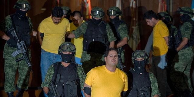 US News Accused drug trafficker Jose Rodolfo Escajeda, center, presented to the media in Mexico City, in 2009. Rodolfo Escajeda and other members of the Juarez cartel were arrested in Casas Grandes, Mexico. (ALFREDO ESTRELLA/AFP via Getty Images, File)