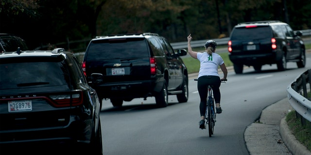 Juli Briskman gestures with her middle finger as a motorcade with President Trump passes by in Virginia in 2017. (Getty Images)