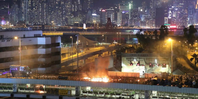 An armored police vehicle, left, approaches a burning barricade built by protestors near the entrance to the Cross Harbour Tunnel in Hong Kong, Sunday, Nov. 17, 2019.