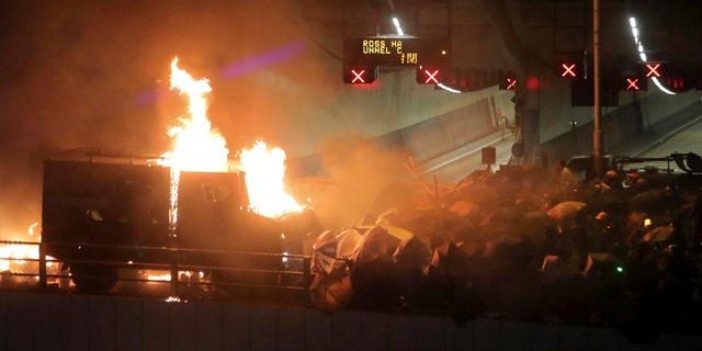 An armored police vehicle catches fire after being hit by molotov cocktails thrown by protestors, at right, on a bridge over a highway leading to the Cross Harbour Tunnel in Hong Kong, Sunday, Nov. 17, 2019.
