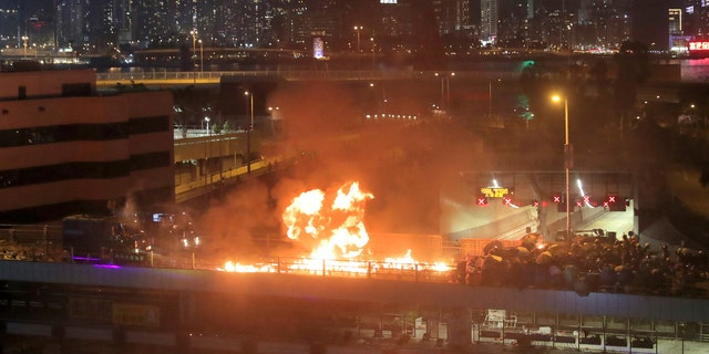 Protestors hurl molotov cocktails as armored police vehicles approach their barricades on a bridge over a highway leading to the Cross Harbour Tunnel in Hong Kong, on Sunday.