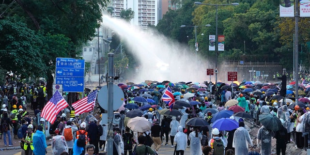 Protesters hold American flags as an armored police vehicle sprays water during a confrontation near the Hong Kong Polytechnic University in Hong Kong, Sunday, Nov. 17, 2019.