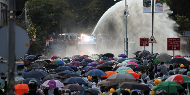 Protesters react as an armored police vehicle sprays water during a confrontation at Hong Kong Polytechnic University in Hong Kong, Sunday, Nov. 17, 2019.