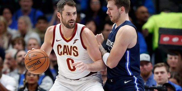 Cleveland Cavaliers forward Kevin Love (0) works against Dallas Mavericks forward Luka Doncic (77) for a shot opportunity in the first half of an NBA basketball game in Dallas, Friday, Nov. 22, 2019. (AP Photo/Tony Gutierrez)