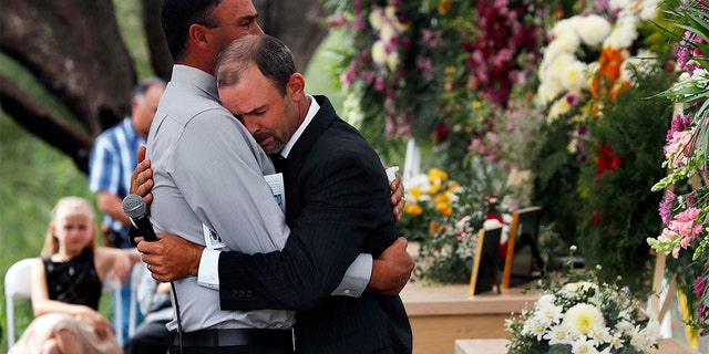 Men embrace next to the coffins of Dawna Ray Langford, 43, and her sons Trevor, 11, and Rogan, 2, who were killed by drug cartel gunmen, during the funeral at a family cemetery in La Mora, Sonora state, Mexico, Thursday, Nov. 7, 2019. Three women and six of their children, all members of the extended LeBaron family, died when they were gunned down in an attack while traveling along Mexico's Chihuahua and Sonora state border on Monday.