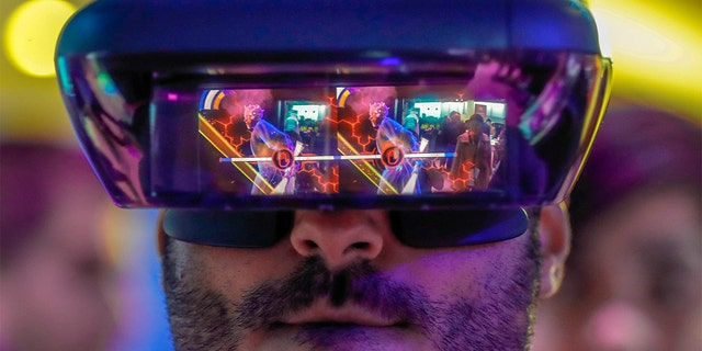 A visitor tries out Lenovo augmented reality glasses with the Star Wars Jedi Challenges during the Mobile World Congress in Barcelona, Spain, February 26, 2018. REUTERS/Yves Herman TPX IMAGES OF THE DAY - RC1EAA1E2450
