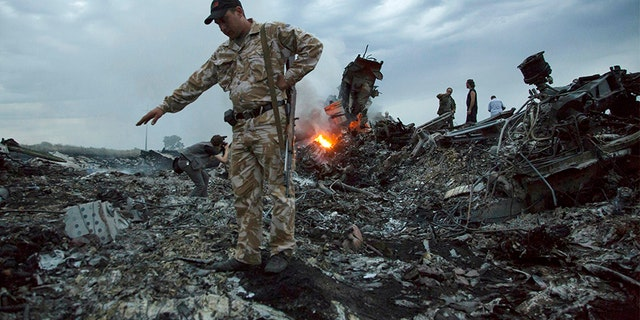 People walk amongst the debris at the crash site of the MH17 passenger plane near the village of Grabovo, Ukraine, in July 2014.