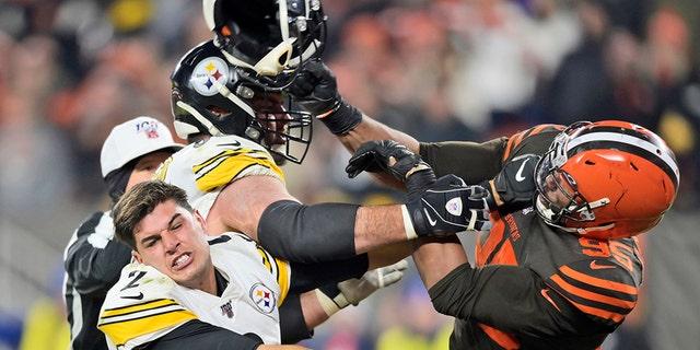 Cleveland Brown's defensive end Myles Garrett (95) hits Pittsburgh Steelers quarterback Mason Rudolph (2) in Cleveland with a helmet during the second half of an NFL football game Thursday, November 14, 2019. (AP Photo / David Richard)