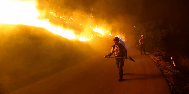 Firefighters walks on a road leading to a residence as the Maria Fire burns on a hillside Thursday, Oct. 31, 2019, in Somis, Calif. (AP Photo/Marcio Jose Sanchez)