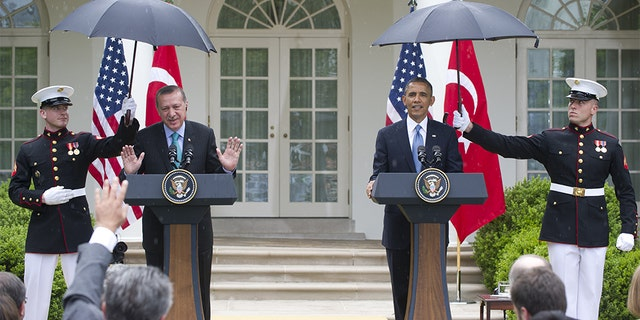 Former President Barack Obama and Turkish Prime Minister Recep Erdogan hold a joint press conference in the Rose Garden in 2013 as Marines shield them from the rain. (SAUL LOEB/AFP via Getty Images, File)