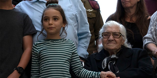 Melpomeni Dina holding the hand of an Israeli girl during a reunion at the Yad Vashem Holocaust memorial in Jerusalem on Sunday.