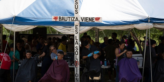Volunteers giving migrants free haircuts at a camp near a legal port of entry bridge in Matamoros, Mexico, last month. (AP Photo/Fernando Llano, File)