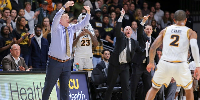 VCU coach Mike Rhoades, left, and other players on the VCU bench react to a play during the second half of an NCAA college basketball game against North Texas in Richmond, Va., Friday, Nov. 8, 2019. (AP Photo/Parker Michels-Boyce)