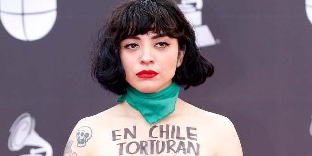 """Mon Laferte arrives at the 20th Latin Grammy Awards with """"En Chile torturan violan y matan"""" written on her body on Thursday, Nov. 14, 2019, at the MGM Grand Garden Arena in Las Vegas. (Photo by Eric Jamison/Invision/AP)"""