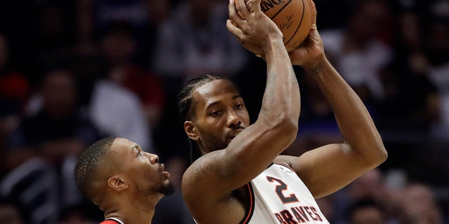 Los Angeles Clippers' Kawhi Leonard (2) is defended by Portland Trail Blazers' Damian Lillard during the first half of an NBA basketball game Thursday, Nov. 7, 2019, in Los Angeles. (AP Photo/Marcio Jose Sanchez)