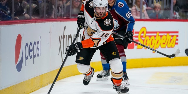 Anaheim Ducks center Adam Henrique (14) moves the puck against Colorado Avalanche left wing Andre Burakovsky (95) during the second period of an NHL hockey game, Saturday, Oct. 26, 2019, in Denver. (AP Photo/Jack Dempsey)