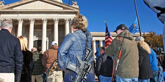 Leslie Nessmith, center, of Edmond, Okla., attends a rally at the state Capitol to mark the start of a new law that allows most adults in Oklahoma to carry a firearm in public without a background check or training. (AP Photo/Sue Ogrocki)