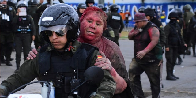 Police rescue Vinto mayor Patricia Arce Guzman on a motorcycle after people threw paint and dirt on her following a fire in Vinto's Town Hall, Quillacollo, Bolivia, November 6, 2019.