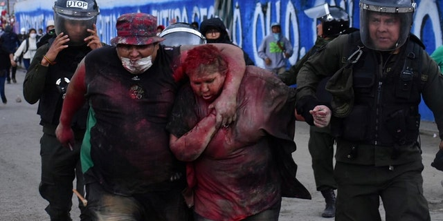 Police rescue Vinto mayor Patricia Arce Guzman after people threw paint and dirt on her following a fire in Vinto's Town Hall, Quillacollo, Bolivia, November 6, 2019, in this image obtained from Los Tiempos Bolivia social media.