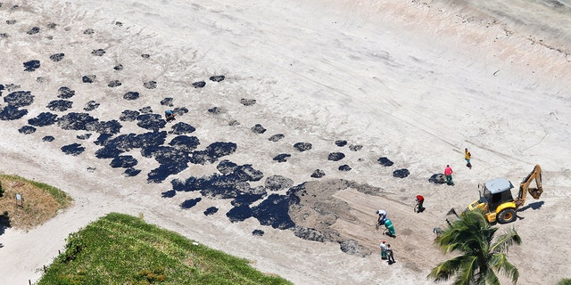 Crews clean up part of the oil spill that reached Peroba beach in northeastern Brazil. (Reuters)