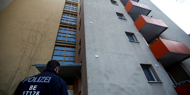 A German police officer stood outside the house of a Syrian man suspected of exchanging bomb-building material after the man's arrest Tuesday in Berlin. (REUTERS/Hannibal Hanschke)
