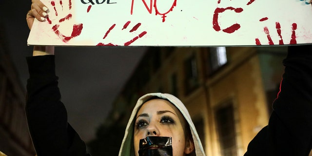 A protester with her mouth covered with tape holds a placard during a demonstration against a Spanish court which sentenced five of six men accused of gang-raping a 14-year-old girl to 10 to 12 years in prison for sexually abusing the minor, but acquitted them of rape, outside the Justice Ministry in Madrid, Spain, in November 2019. (Reuters)