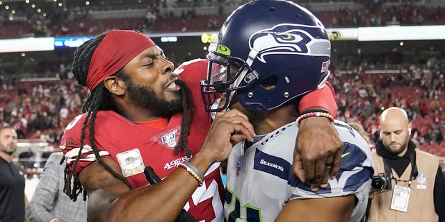San Francisco 49ers cornerback Richard Sherman, left, hugs Seattle Seahawks middle linebacker Bobby Wagner after an NFL football game in Santa Clara, Calif., Monday, Nov. 11, 2019. The Seahawks won 27-24 in overtime.