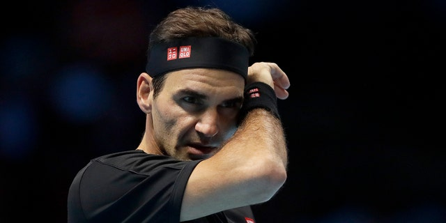 Roger Federer of Switzerland wipes his face after he plays a return to Stefanos Tsitsipas of Greece during their ATP World Tour Finals semifinal tennis match at the O2 Arena in London, Saturday, Nov. 16, 2019.