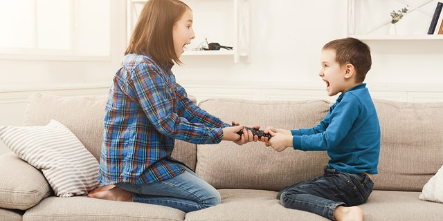 Siblings fighting over remote control at home, brother and sister have quarrel, copy space. (Photo: iStock)