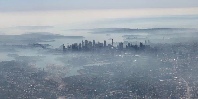 An image taken on a smartphone from a plane window shows smoke haze blanketing Sydney on, November 19, 2019.