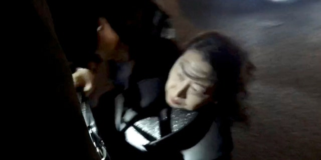 Hong Kong Justice Secretary Teresa Cheng gets up after falling when protesters surrounded her in London, on Nov. 14, 2019, in this still image from video obtained via social media. Chloe Leung via REUTERS