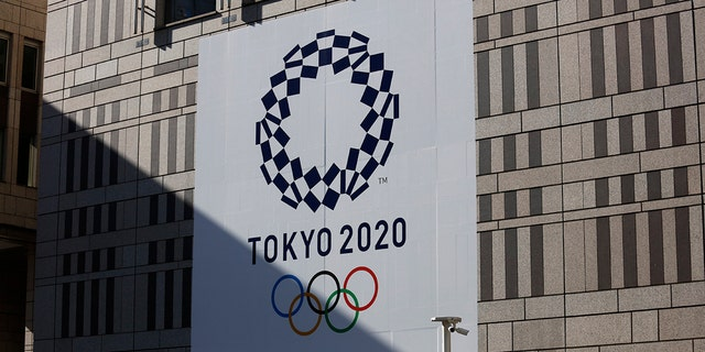 A man walks past a large Tokyo 2020 banner hanging on the facade of the Tokyo Metropolitan Government building Thursday, Nov. 21, 2019, in Tokyo. The French language has been almost invisible during the drawn-out preparations for next year's Tokyo Olympics.(AP Photo/Jae C. Hong)