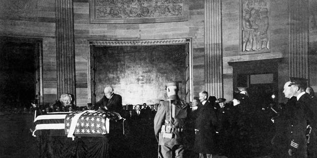 President Warren G. Harding places a wreath on the casket of an unknown soldier from World War I in the rotunda of the U.S. Capitol, Nov. 11, 1921 in Washington. (AP Photo)